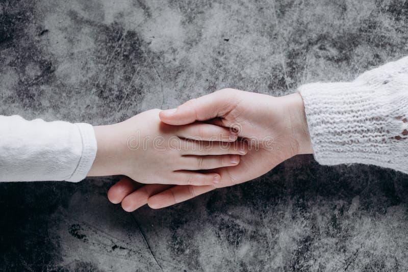 Vue haute étroite de famille tenant des mains, aimant s'inquiétant l'enfant de soutien de mère Coup de main et concept d'espoir photo stock