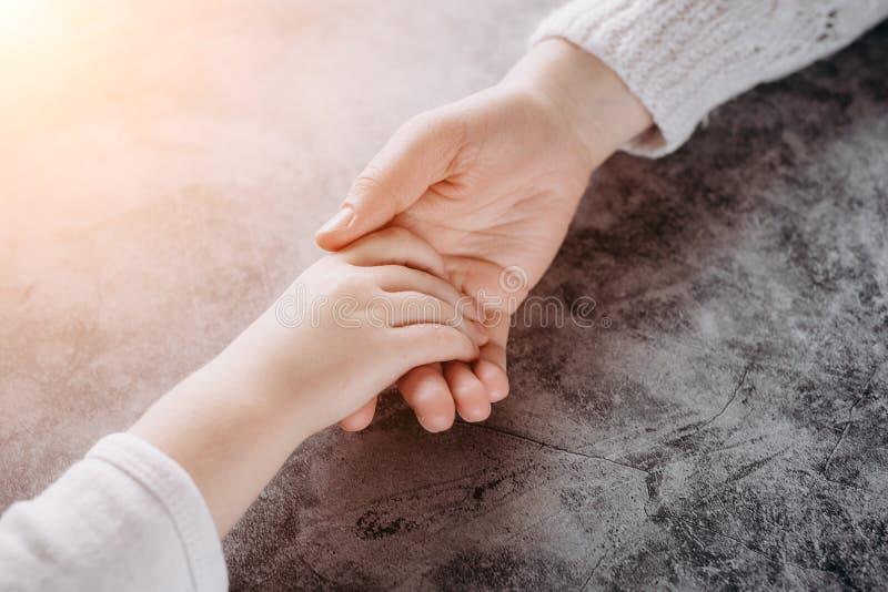 Vue haute étroite de famille tenant des mains, aimant s'inquiétant l'enfant de soutien de mère Coup de main et concept d'espoir images stock