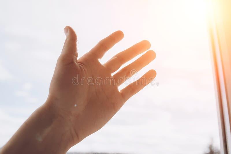 Vue haute étroite de main sur le fond du soleil Concept de coup de main et d'espoir et jour international images libres de droits