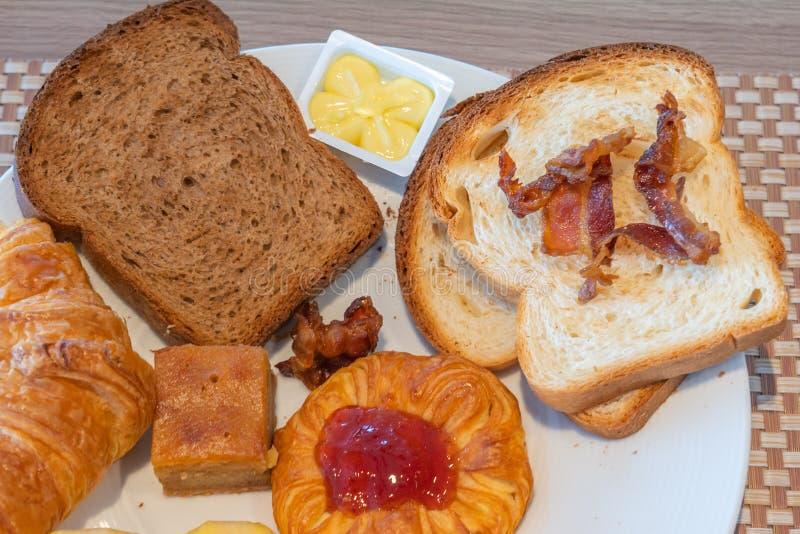 Vue haute étroite de pain brun, croissant, beurre, confiture de fraise image libre de droits