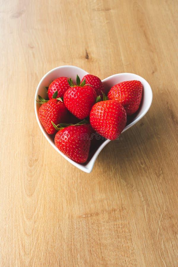Vue haute ?troite des fraises et d'une fleur rouge dans une cuvette en forme de coeur blanche sur le fond en bois image stock