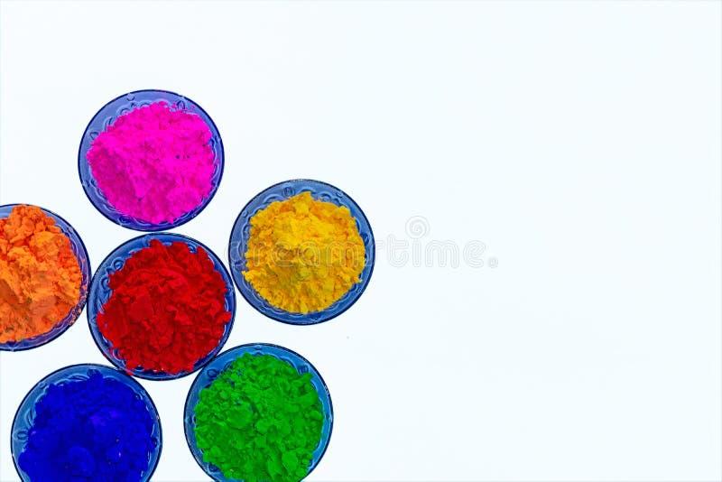 Vue haute étroite des poudres organiques colorées de Holi dans des cuvettes bleues de couleur images stock