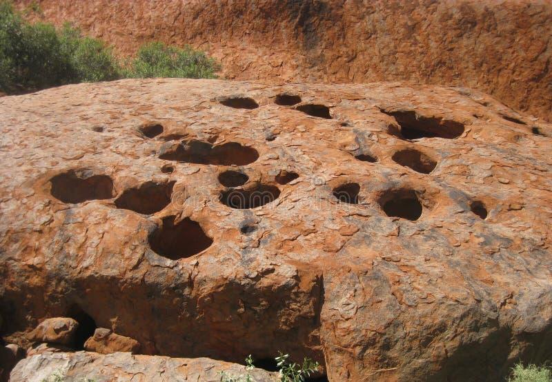 Vue haute étroite des trous dans la roche de la promenade basse d'Uluru images stock