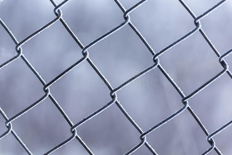 Vue haute étroite du gel gelé de barrière en métal couvert dans le jour d'hiver nuageux Orientation molle photo libre de droits