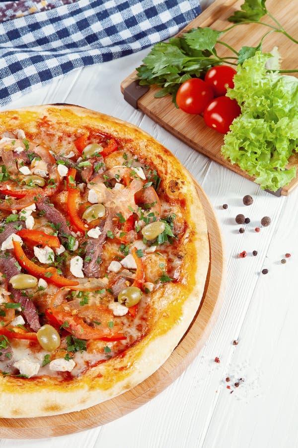 Vue haute étroite sur la pizza sur le fond en bois blanc avec des ingridients photographie stock