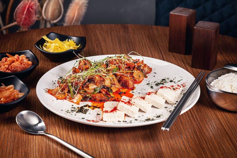 Vue haute étroite sur le porc coupé en tranches coréen traditionnel en sauce aigre-doux avec des feuilles de laitue La viande a s photographie stock