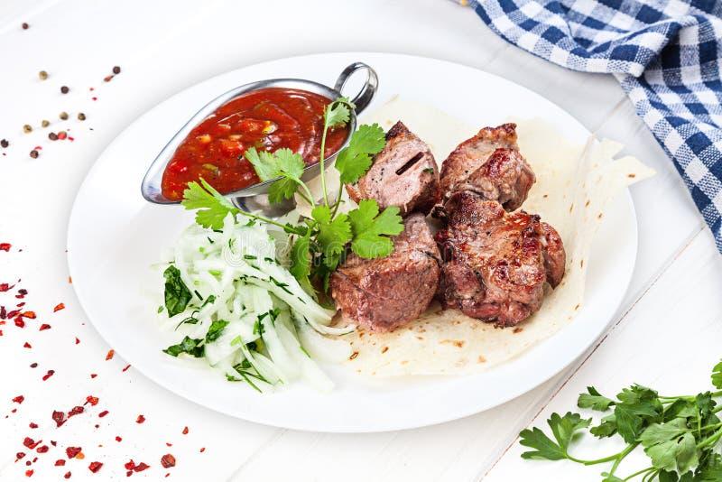 Vue haute étroite sur servi cuit sur le porc de gril viande de shashlik ou de barbecue sur le pain pita Chiche-kebab, cuisine géo photographie stock