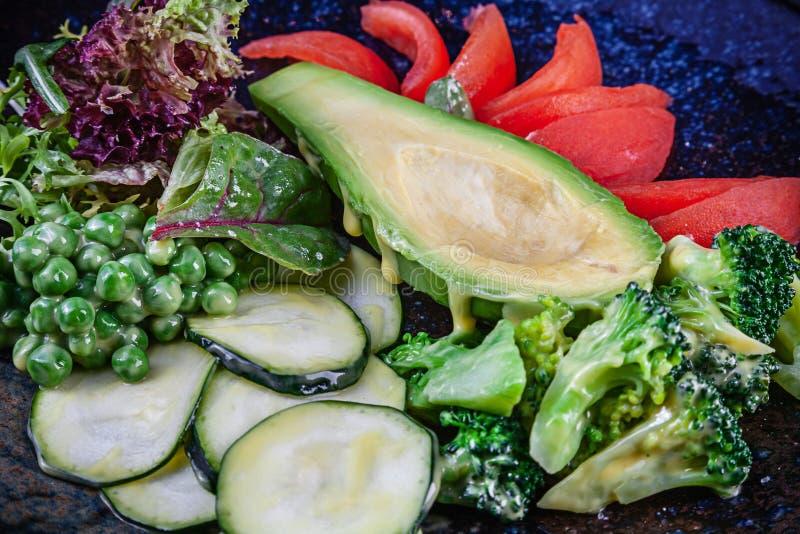 Vue haute ?troite sur la salade verte avec l'avocat dans servi dans le plat texturis? noir sur le fond fonc? Nourriture plate de  image libre de droits