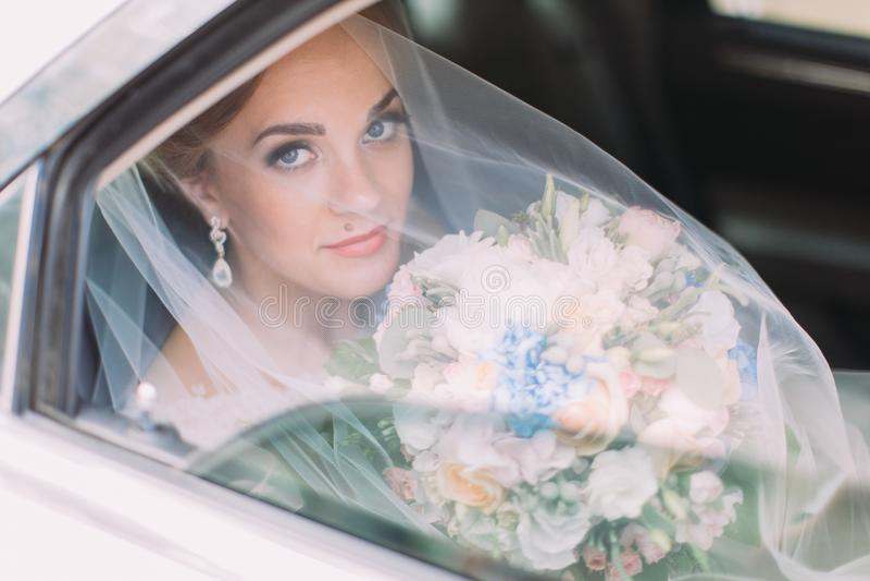 Vue horizontale de la jeune mariée sous le voile tenant le bouquet de mariage tout en se reposant dans la voiture image libre de droits