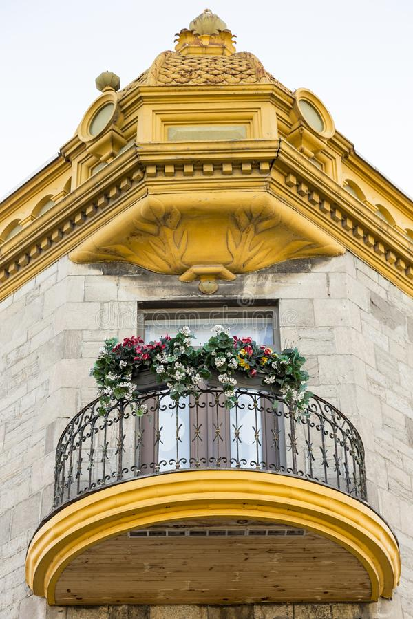 Vue inférieure de balcon de grume et en métal et de corniche d'or fleurie photo libre de droits