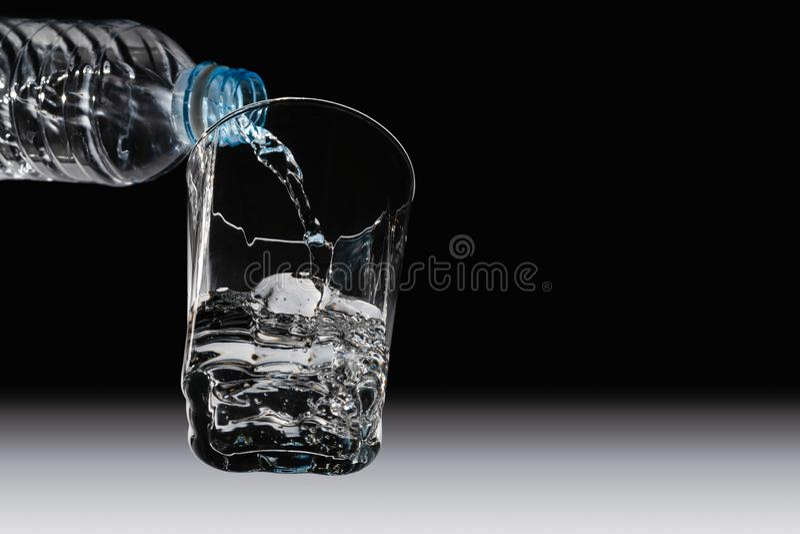Vue inférieure de l'eau potable étant versée de la bouteille photo libre de droits