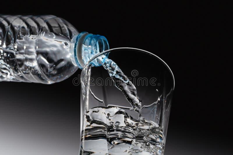 Vue inférieure de l'eau potable étant versée de la bouteille photos stock