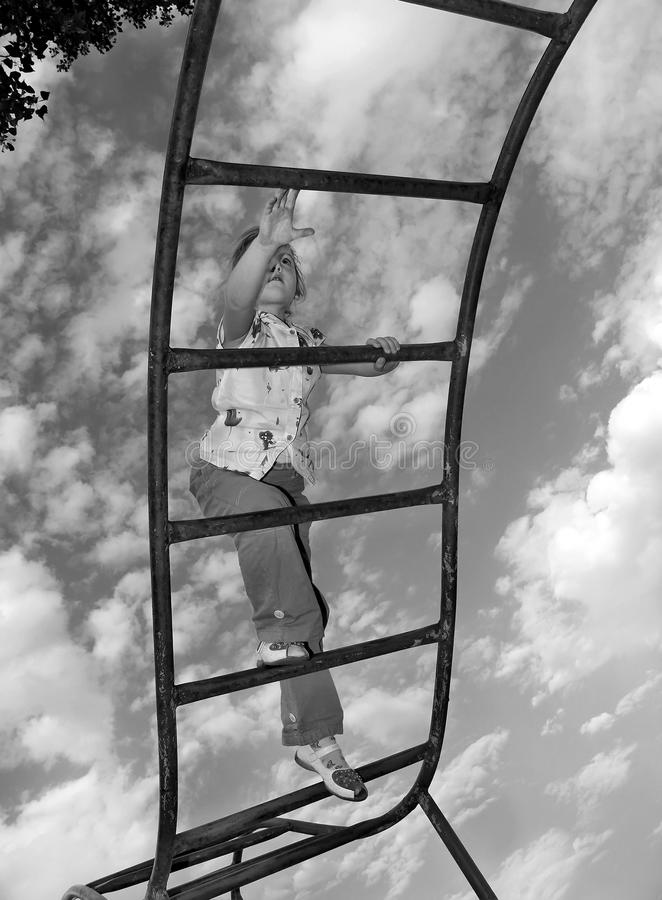 Vue inférieure de la petite fille montant les escaliers sur le fond de ciel image stock