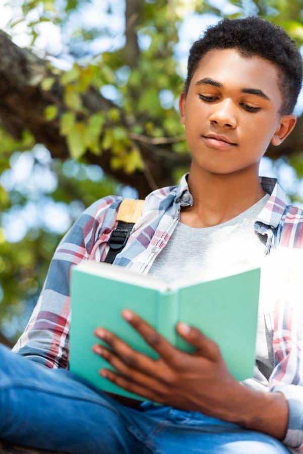 vue inférieure de livre de lecture de l'adolescence focalisé d'étudiant photographie stock libre de droits