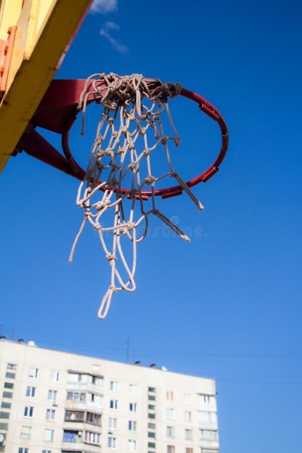 Vue inférieure de plan rapproché de vieux cercle de basket-ball au-dessus de ciel bleu clair et de bâtiment moderne image libre de droits