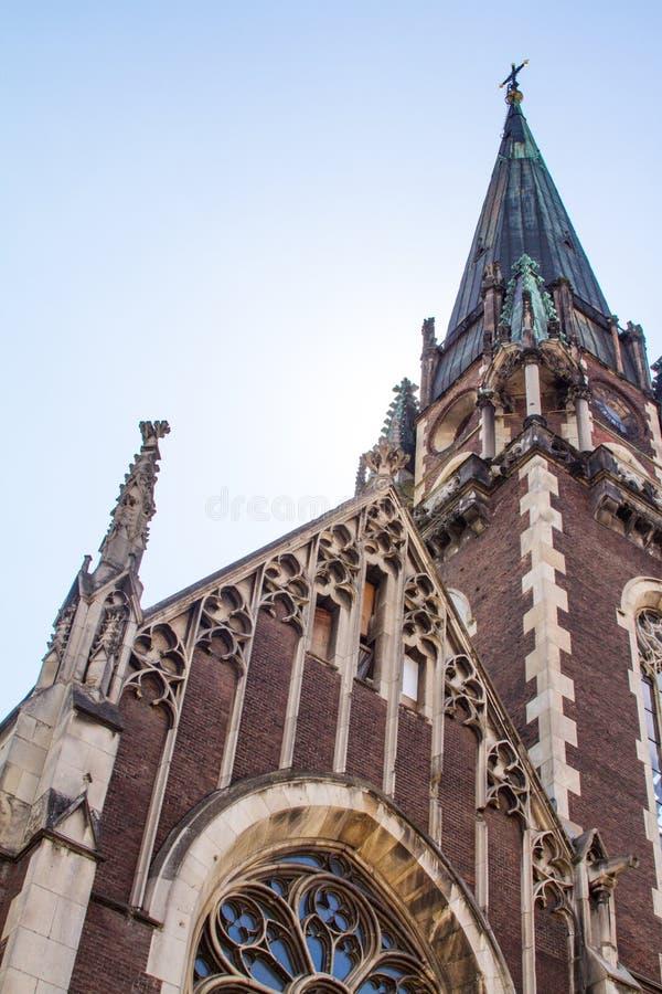 Vue inférieure des détails du toit de la cathédrale gothique à Lviv, Ukraine avec le ciel bleu sur le fond images stock