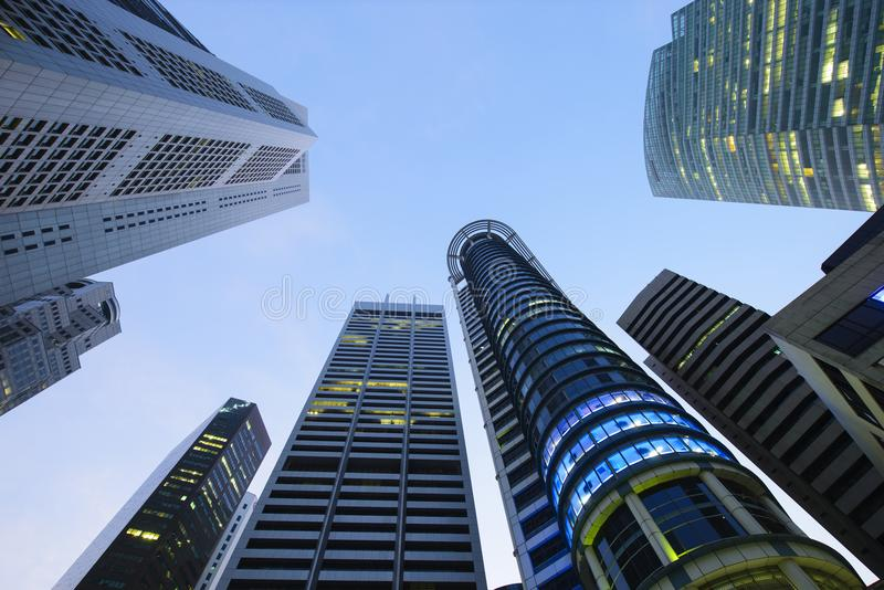 Vue inférieure des gratte-ciel modernes au district des affaires contre le ciel bleu photographie stock