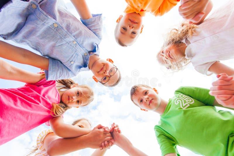 Vue inférieure du groupe d'écoliers heureux se tenant en cercle photographie stock