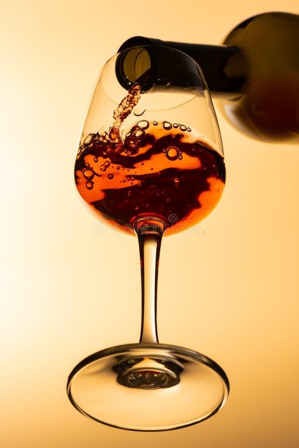 Vue inférieure du vin rouge étant versé de la bouteille de vin image stock