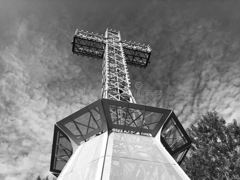 Vue inférieure noire et blanche d'une croix industrielle énorme en métal encadrée par des arbres et des nuages images stock