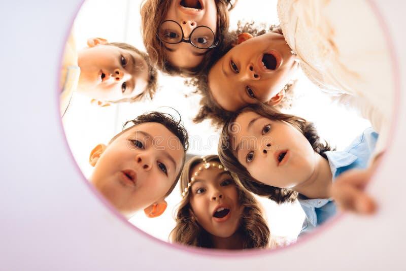 Vue inférieure Regard étonné d'enfants dans le boîte-cadeau rond Concept des vacances du ` s d'enfants image libre de droits
