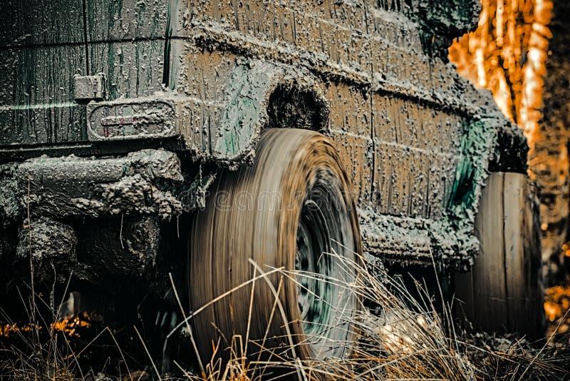 Vue inf?rieure ? la grande roue de voiture tous terrains sur la route de campagne et le contexte de montagnes Mudding off-roading images stock