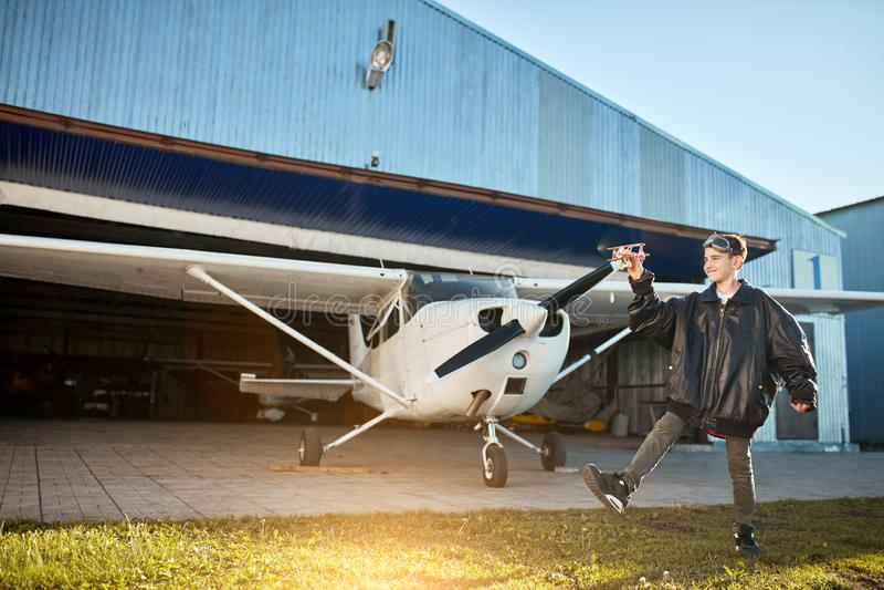 Vue intégrale de garçon jouant avec le petit avion de jouet devant le jet privé léger d'air photographie stock libre de droits