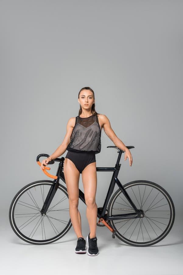 vue intégrale de jeune femme sensuelle se tenant avec la bicyclette et regardant l'appareil-photo images stock
