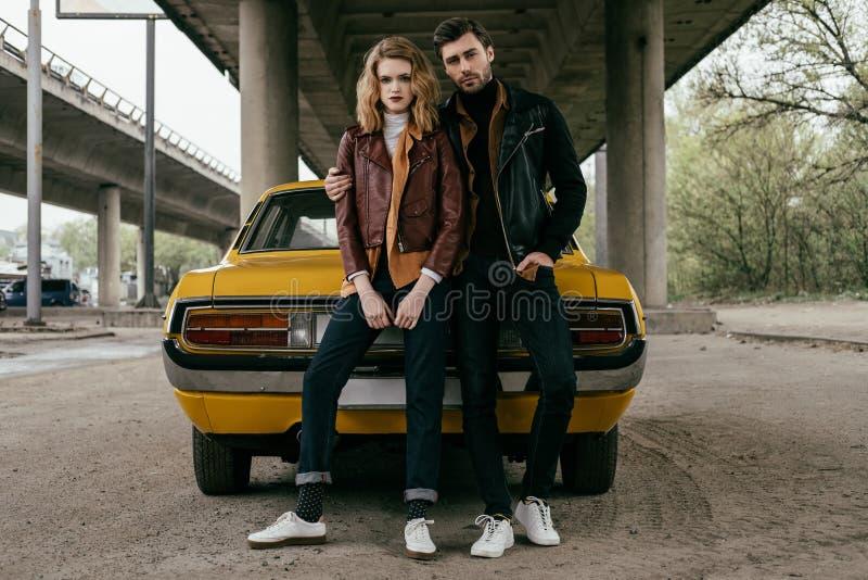vue intégrale de jeunes couples dans des vestes en cuir se reposant sur la voiture démodée jaune et le regard photographie stock