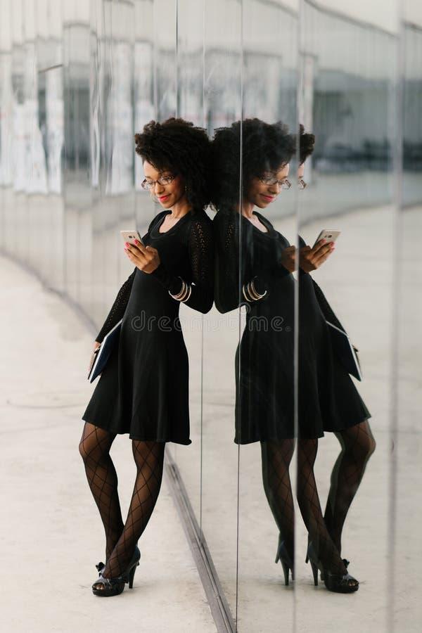 Vue intégrale de la femme d'affaires à la mode à l'aide du téléphone portable photos stock