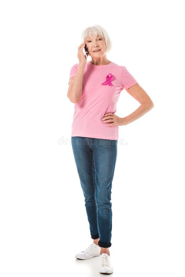 vue intégrale de la femme supérieure dans le T-shirt rose avec le ruban de conscience de cancer du sein parlant par le smartphone image stock