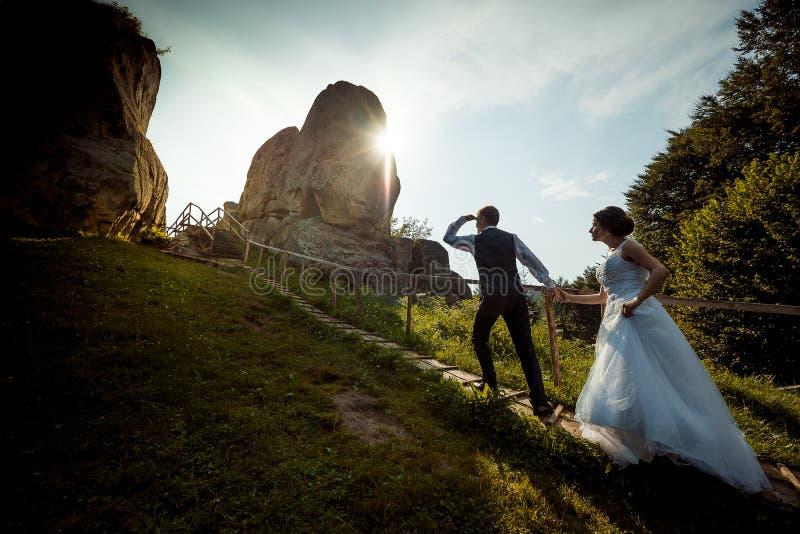Vue intégrale du marié elegent menant la belle jeune jeune mariée par la main le long des escaliers en bois dans l'ensoleillé photographie stock