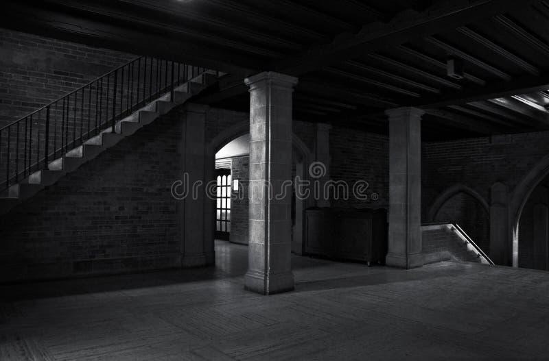 Vue intérieure d'un vieux bâtiment avec des colonnes et d'escalier avec quelques faisceaux lumineux dans l'entourage foncé photos stock