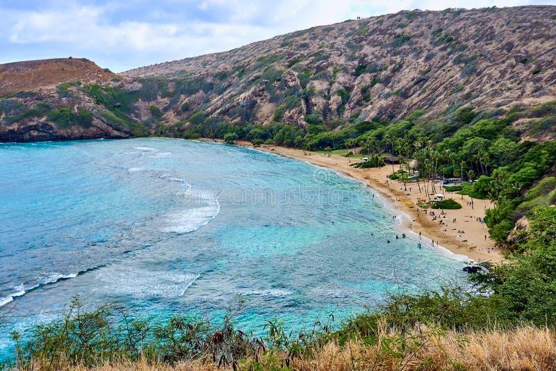 Vue large de la baie et des touristes de Hanauma par la plage et dans les eaux naviguant au schnorchel en Hawaï, Etats-Unis photographie stock