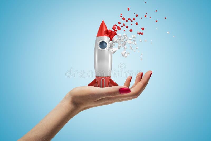 Vue latérale de plan rapproché de la main de la femme faisant face, tenant la fusée de jouet qui démarre au disslove dans les mor photographie stock
