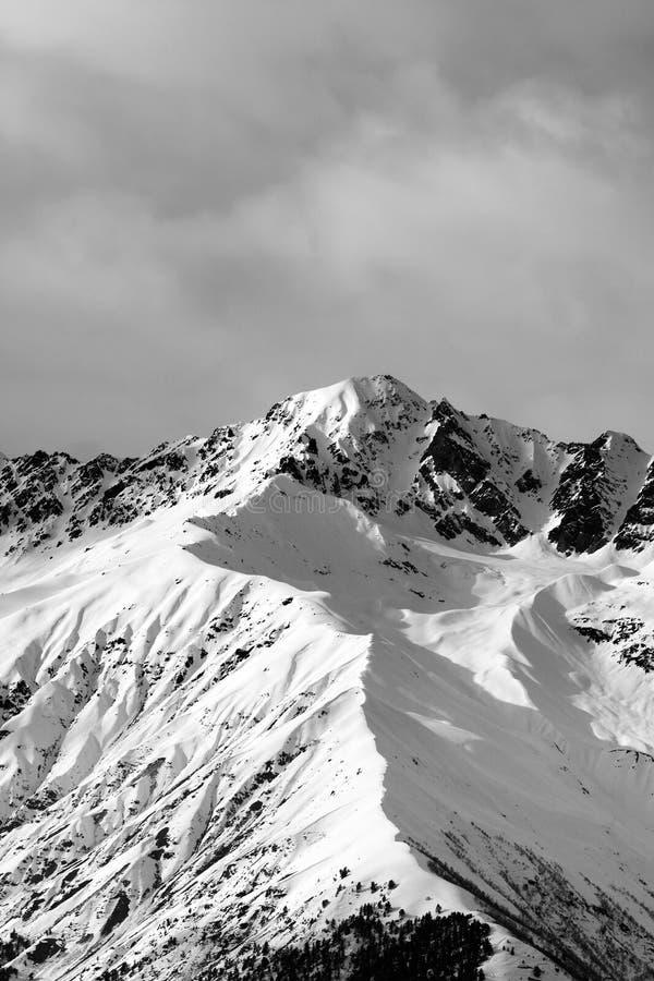Vue noire et blanche sur la montagne ensoleill?e de neige et le ciel nuageux ? la soir?e d'hiver photos stock