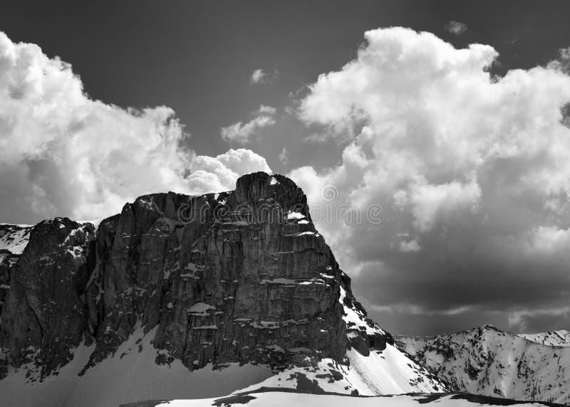 Vue noire et blanche sur les roches et le ciel neigeux avec des nuages dans gentil photo libre de droits