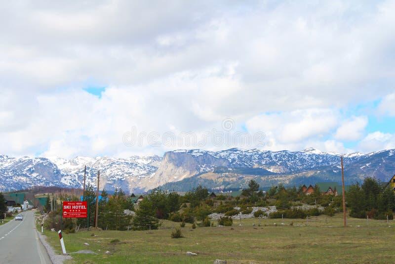 Vue panoramique avec de vieilles maisons rurales du beau plateau vert de la montagne de Zabljak ? la montagne neigeuse de Durmito photos libres de droits