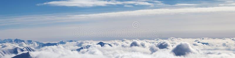 Vue panoramique d'avion des montagnes neigeuses avec les nuages ensoleillés photo libre de droits