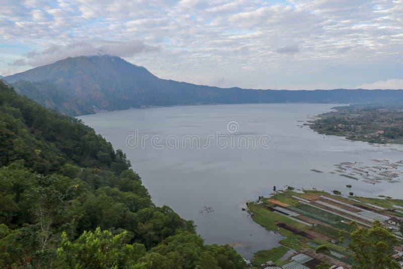 Vue panoramique d'un lac entour? par la montagne, paysage tropical avec les nuages color?s dans le ciel Danau Batur, Gunung Batur photo stock