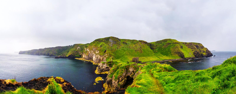 Vue panoramique d'une côte et des monsieurs de chaussée avec le château et la mer de Kinbane photographie stock libre de droits