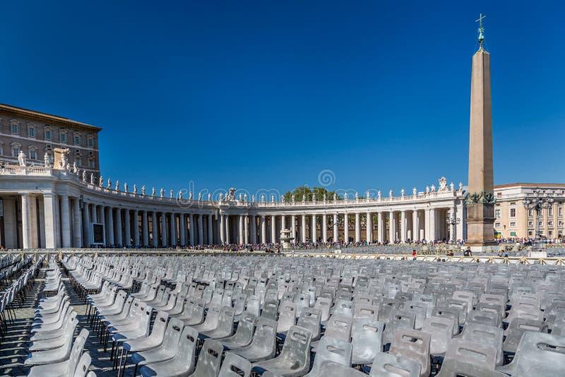 Vue panoramique de beaucoup de chaises grises vides sur St Peters Square avec les personnes et le bâtiment de Vatican image stock