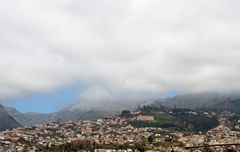 Vue panoramique de Funchal en la Madère avec des maisons entre les collines vertes et les montagnes sous le nuage blanc photo libre de droits