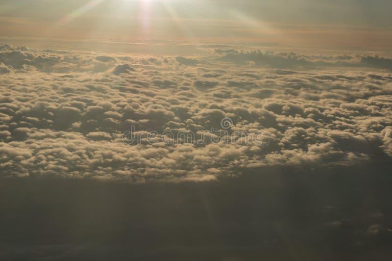 Vue panoramique de la fen?tre du vol plat au-dessus des nuages soleil-tremp?s photos stock