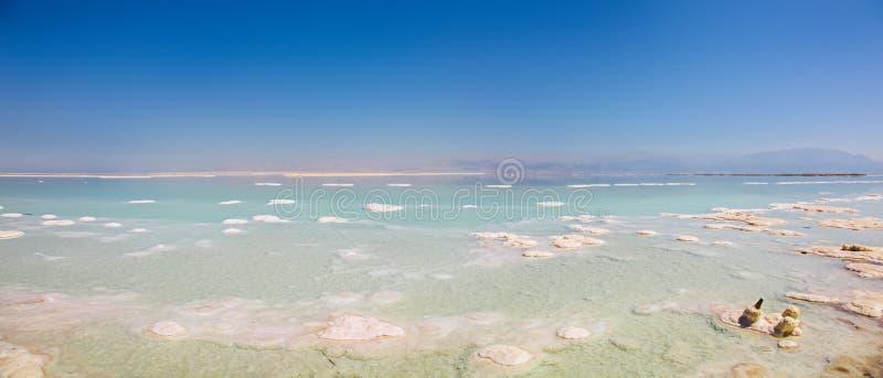 Vue panoramique des bleus renversants et des piles blanches rigides de sel pointillant la mer morte photos stock