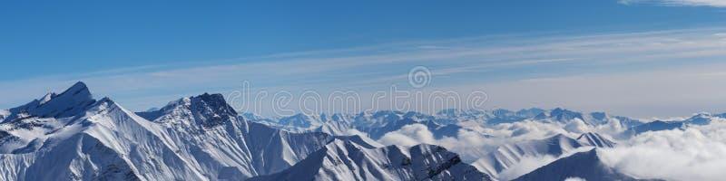 Vue panoramique des montagnes neigeuses et du ciel bleu avec des nuages photos stock