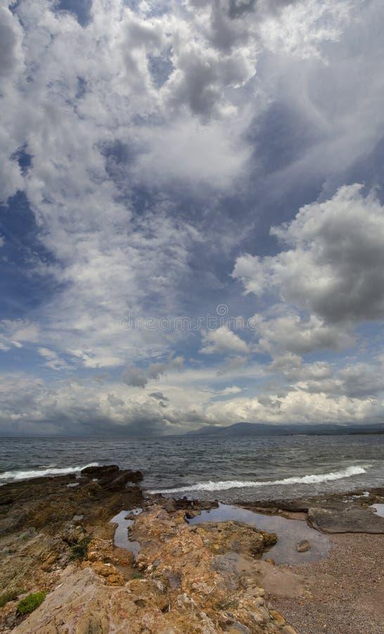 Vue panoramique des nuages d'orage renversants, des vagues et de la plage rocheuse en mer Égée un jour d'été sur l'île d'Evia, GR images libres de droits