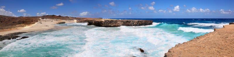 Vue panoramique des vagues se brisantes de turquoise et des falaises rocheuses de Boca Ketu Aruba image stock