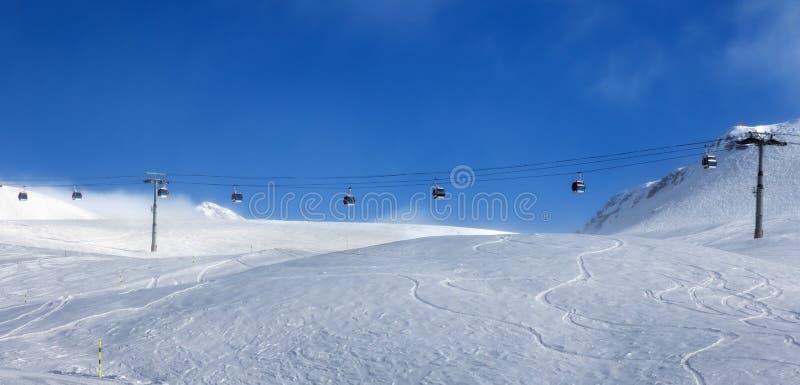Vue panoramique sur l'ascenseur de gondole et pente hors-piste de ski en brouillard à la soirée ensoleillée agréable Montagnes de photos libres de droits