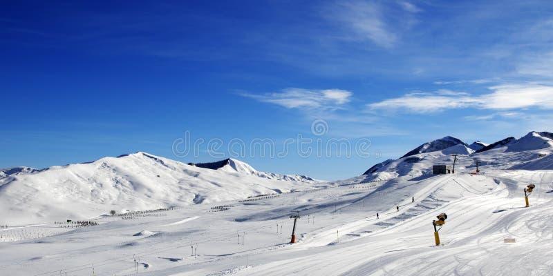 Vue panoramique sur la pente de ski avec snowmaking au jour du soleil image libre de droits